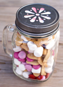 A jar with marshmallows and pink candy