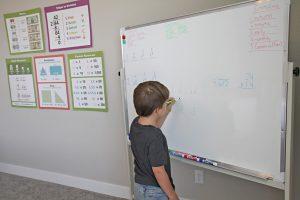 A boy writing on a whiteboard