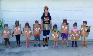 Ms. Aurica with kids in a costume
